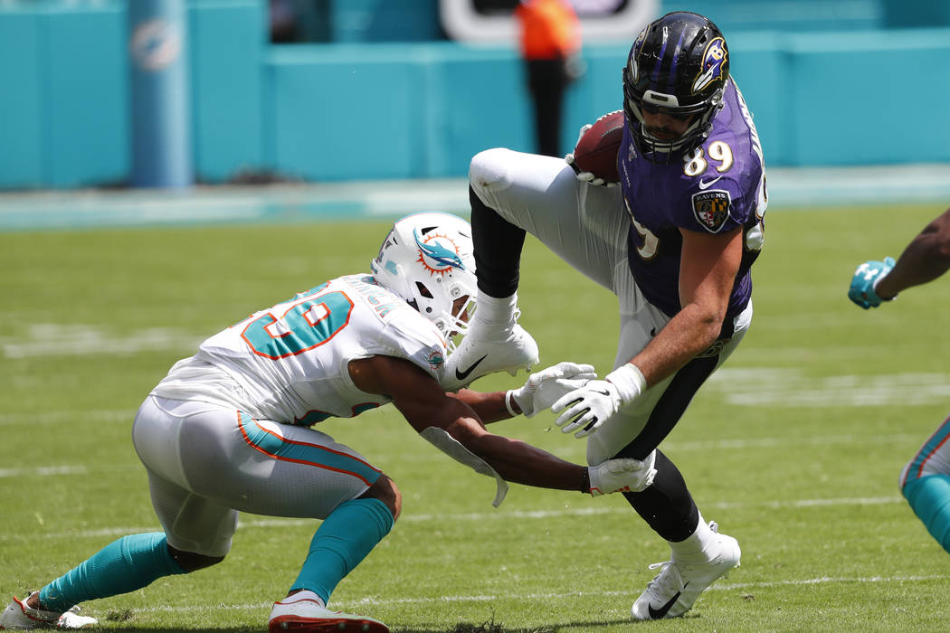 Miami Dolphins free safety Minkah Fitzpatrick (29) tackles Baltimore Ravens tight end Mark Andr ...