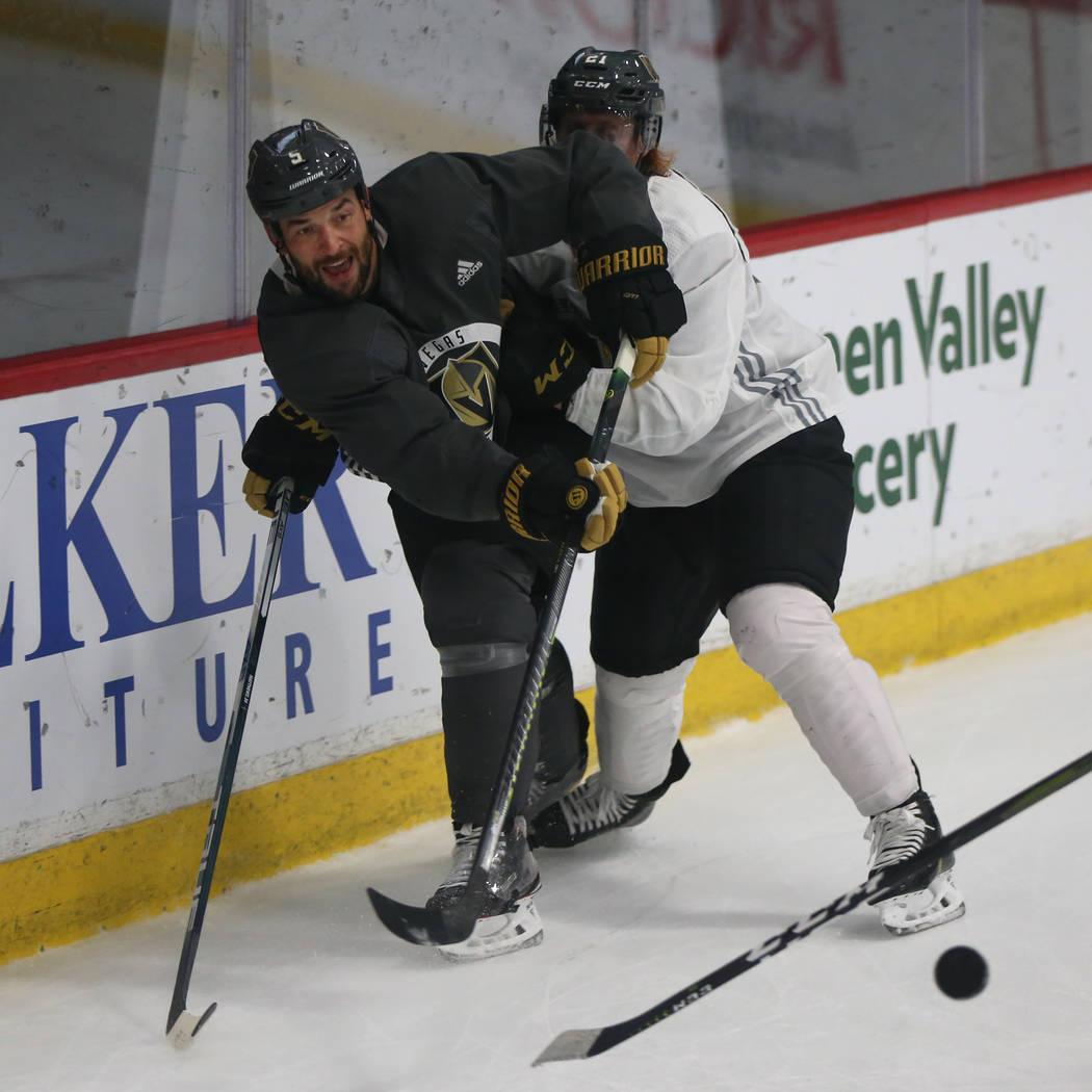 Vegas Golden Knights defenseman Deryk Engelland (5) clears the puck under pressure from center ...