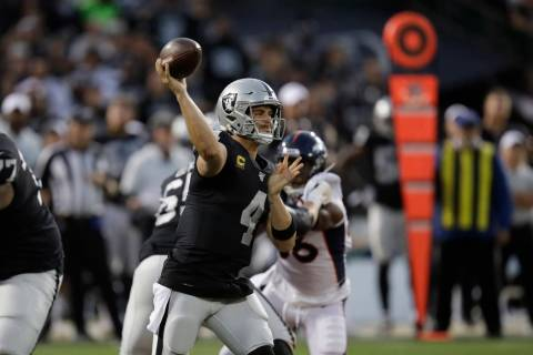 Oakland Raiders quarterback Derek Carr throws during the first half of an NFL football game aga ...