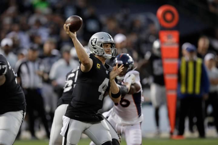 Oakland Raiders quarterback Derek Carr throws during the first half of an NFL football game aga ...