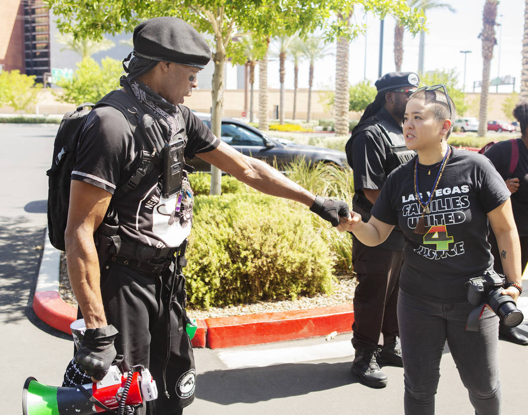Jay Jackson, local chairman of the New Black Panther Party, left, fist bumps to Nissa Tzun, rig ...