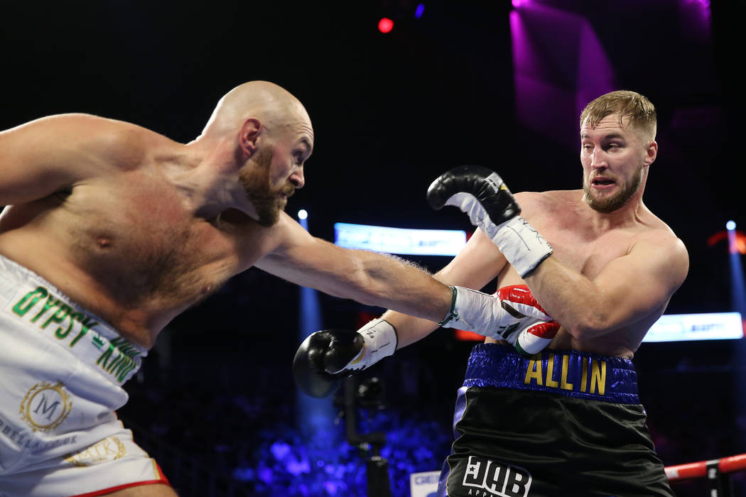Tyson Fury, left, throws a punch against Otto Wallin in the first round of the heavyweight bout ...