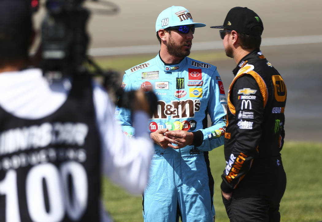 Kyle Busch, left, talks with Kurt Busch before qualifying for a NASCAR Cup Series auto race at ...