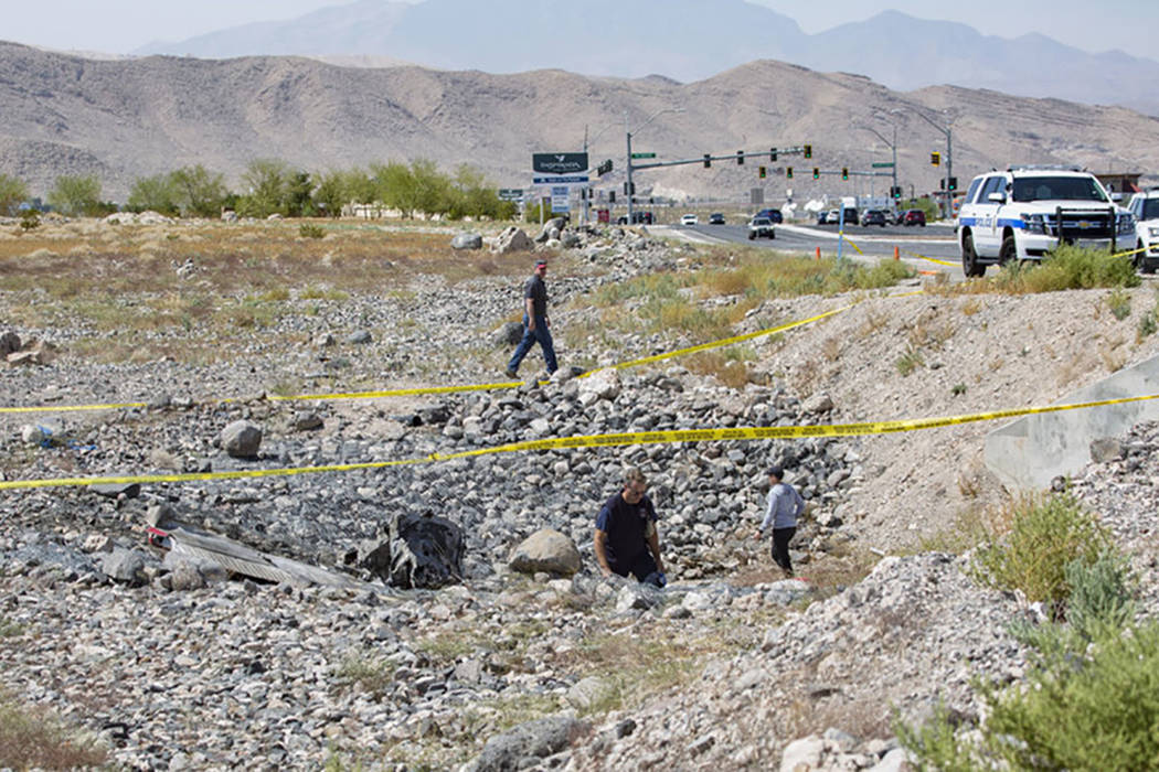Federal Aviation Administration employees investigate the scene of a fatal airplane crash from ...