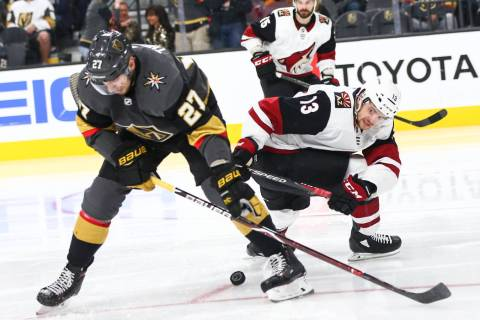 In this file photo, Golden Knights defenseman Shea Theodore (27) tries to get the puck from Ari ...