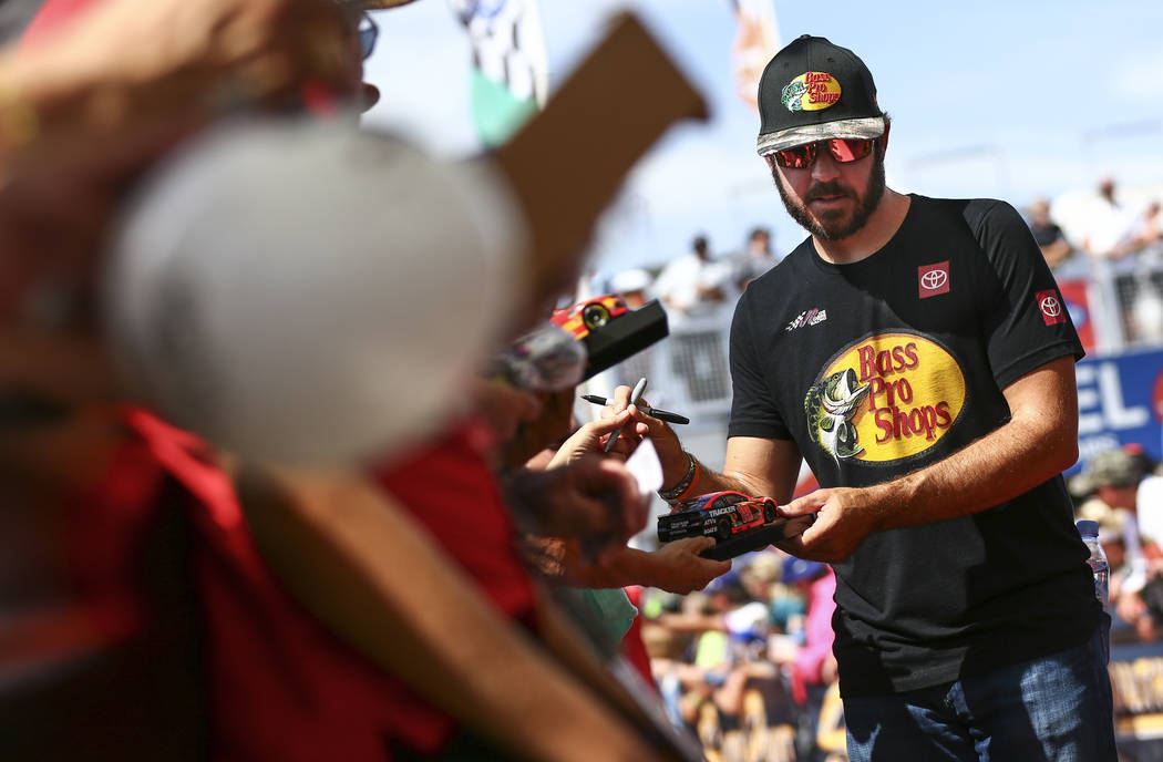 Martin Truex Jr. gives autographs to fans before a NASCAR Cup Series auto race at Las Vegas Mot ...