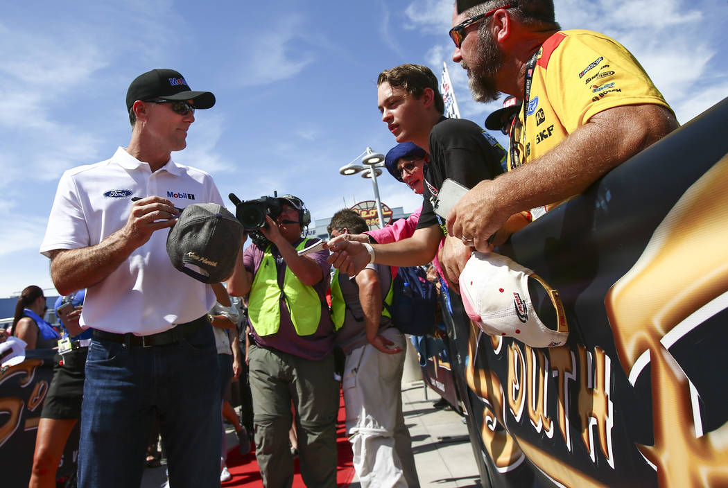Kevin Harvick gives autographs to fans before a NASCAR Cup Series auto race at Las Vegas Motor ...