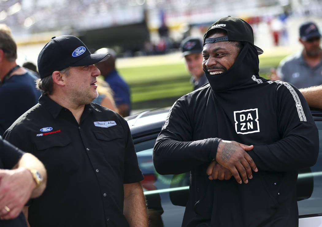 Team owner Tony Stewart, left, talks with former NFL football player Marshawn Lynch before a NA ...