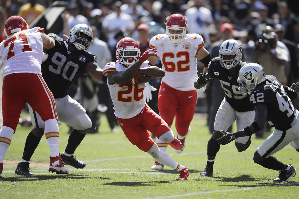 Kansas City Chiefs running back Damien Williams (26) runs with the ball during the first half o ...