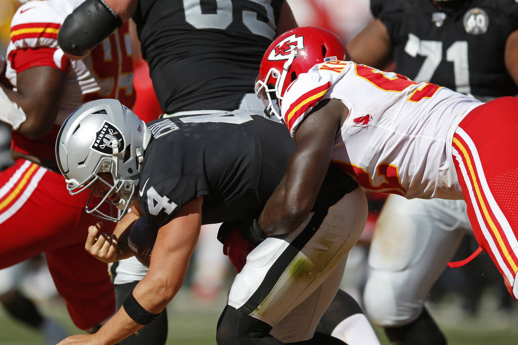 Oakland Raiders quarterback Derek Carr is brought down by Kansas City Chiefs defensive end Tano ...