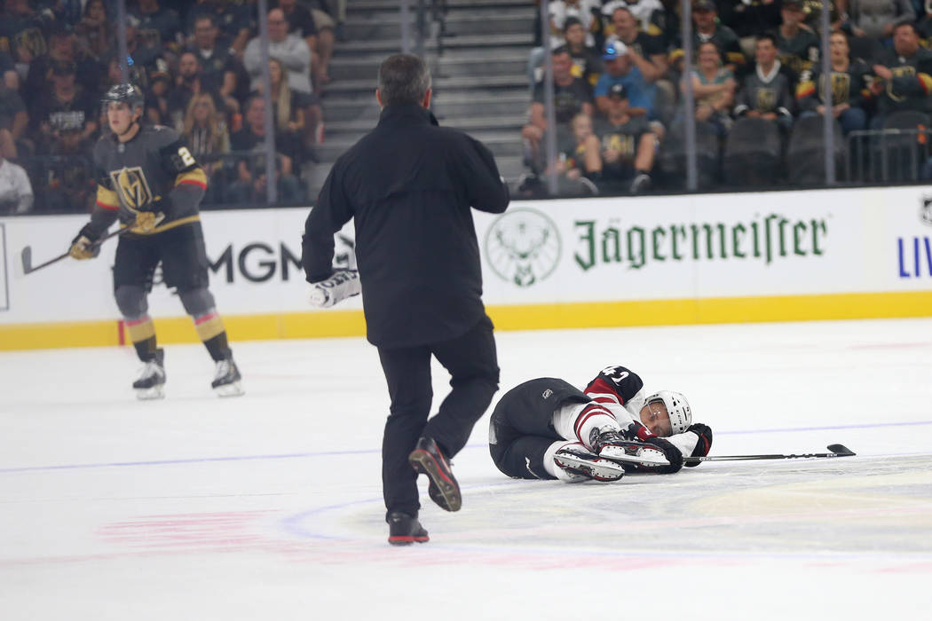 Arizona Coyotes defenseman Aaron Ness (42) falls after taking a hit from Vegas Golden Knights r ...