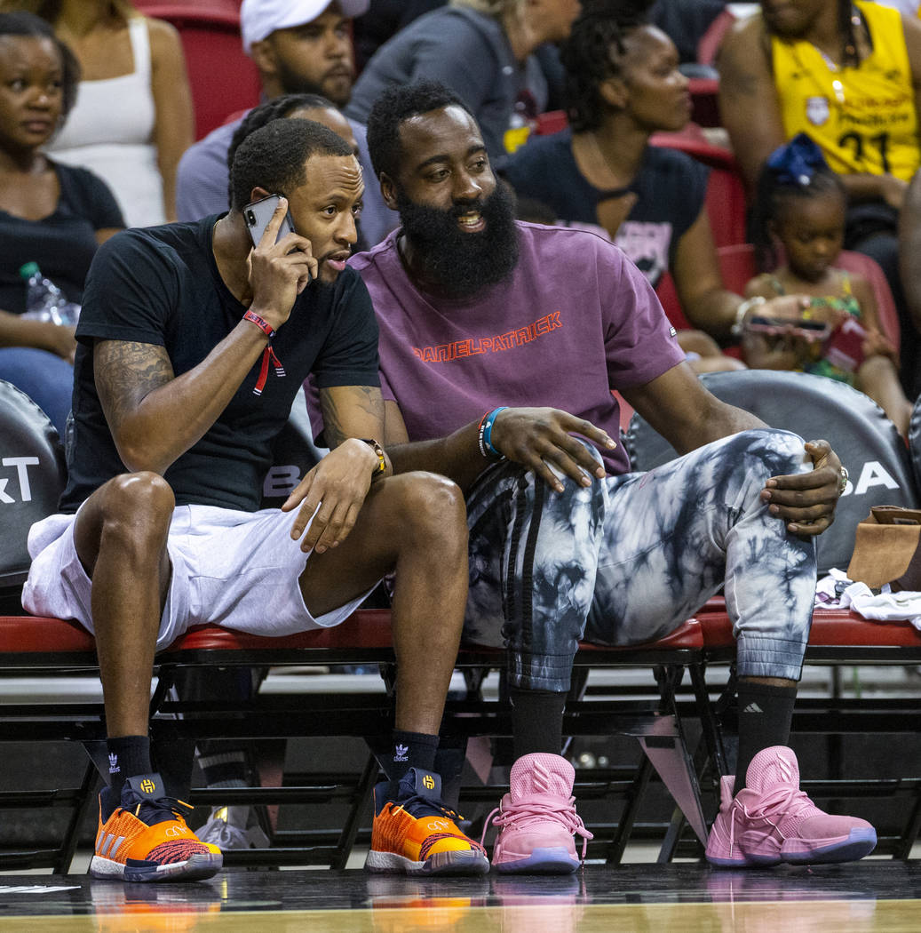 Houston Rockets player James Harden, right, enjoys the game with a companion as the Las Vegas A ...