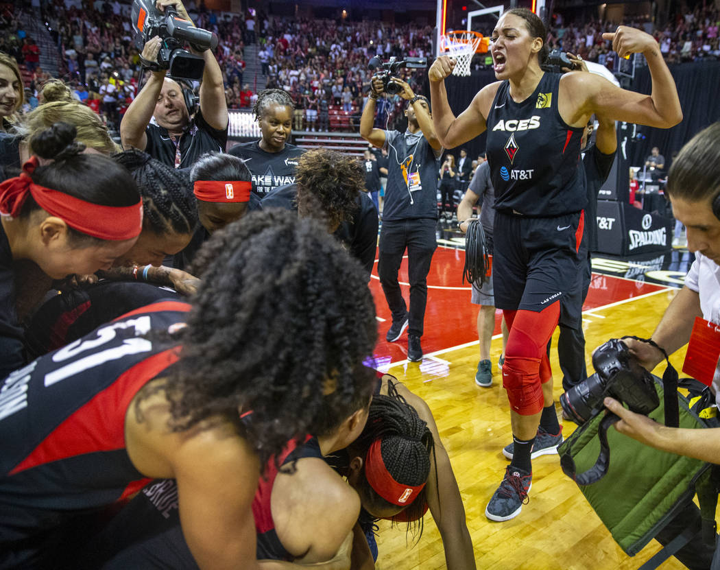 Las Vegas Aces center Liz Cambage (8, right) flexes as her teammates pile up celebrating the vi ...