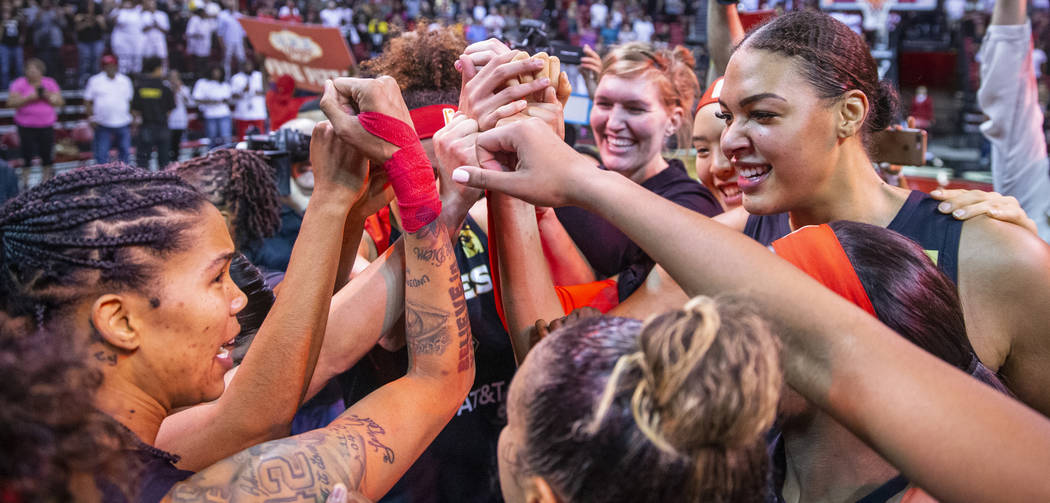 Las Vegas Aces forward Tamera Young (1, left) looks center Liz Cambage (8, right) as teammates ...