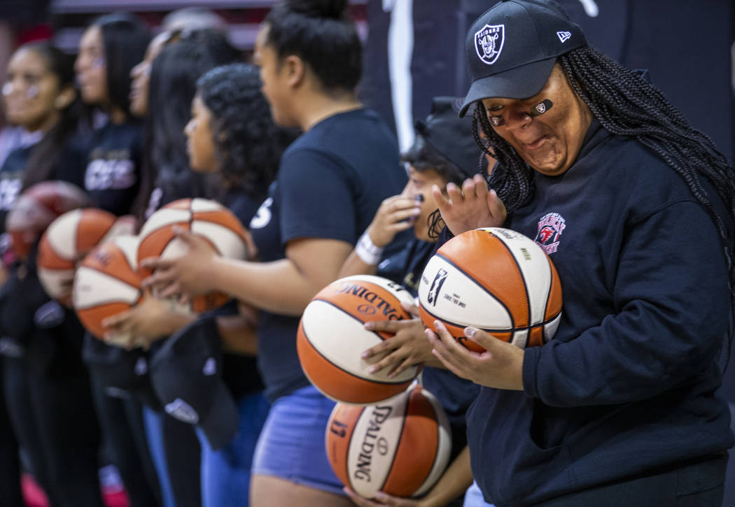 Las Vegas Aces fans are given basketballs by players prior to the first half of their WNBA play ...