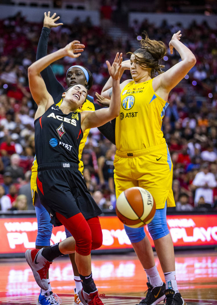 Las Vegas Aces guard Kelsey Plum (10, left) reacts to a hard shot from Chicago Sky guard Kahlea ...