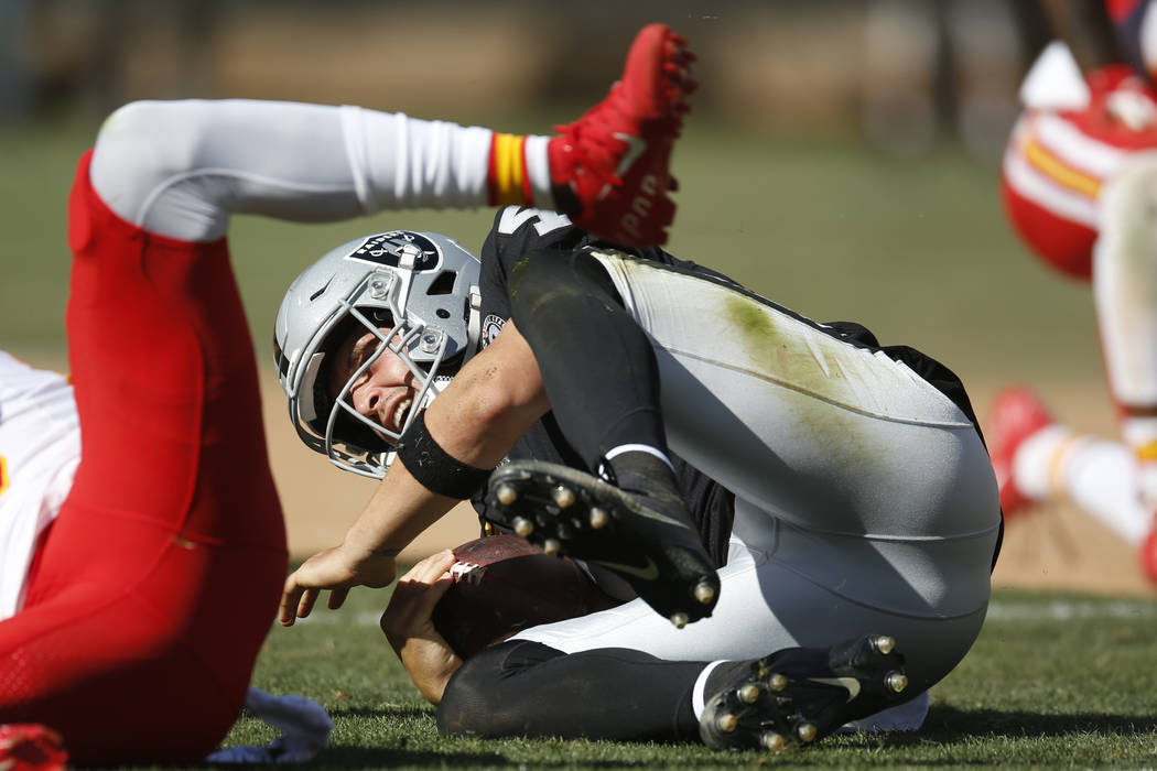 Oakland Raiders quarterback Derek Carr hits the ground after a play during the second half of a ...