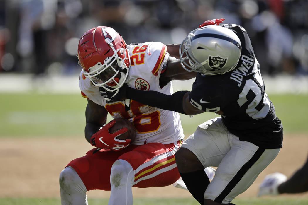 Kansas City Chiefs running back Damien Williams tries to break away from Oakland Raiders free s ...