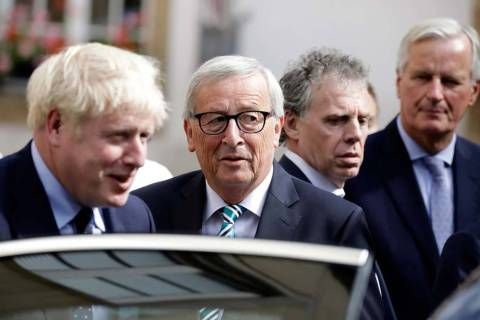 European Commission President Jean-Claude Juncker, center, speaks with British Prime Minister B ...