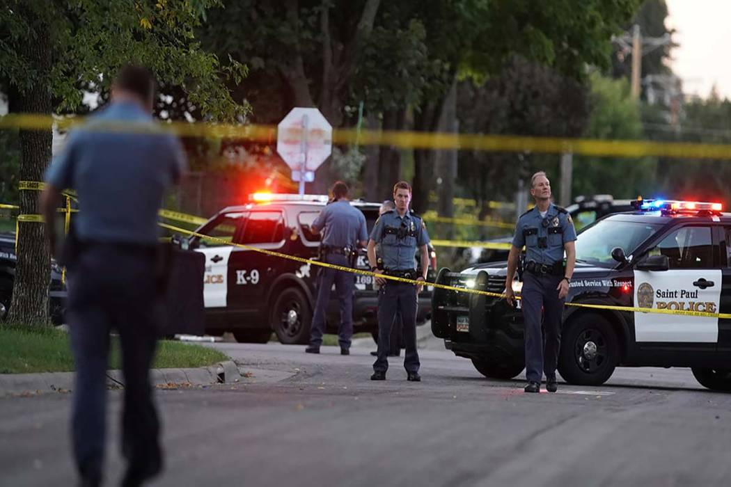 Police officers work the scene of a shooting near North Griggs and Thomas Ave West in St. Paul, ...