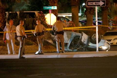 Las Vegas police officers investigate a fatal crash at Flamingo Road and Duneville Street in La ...