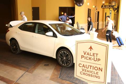 Hotel guests at Wynn Las Vegas prepare to load their luggage into their car at valet parking pi ...