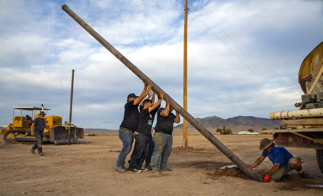 A crew works to set another pole for wireless internet service about the Alienstock festival gr ...