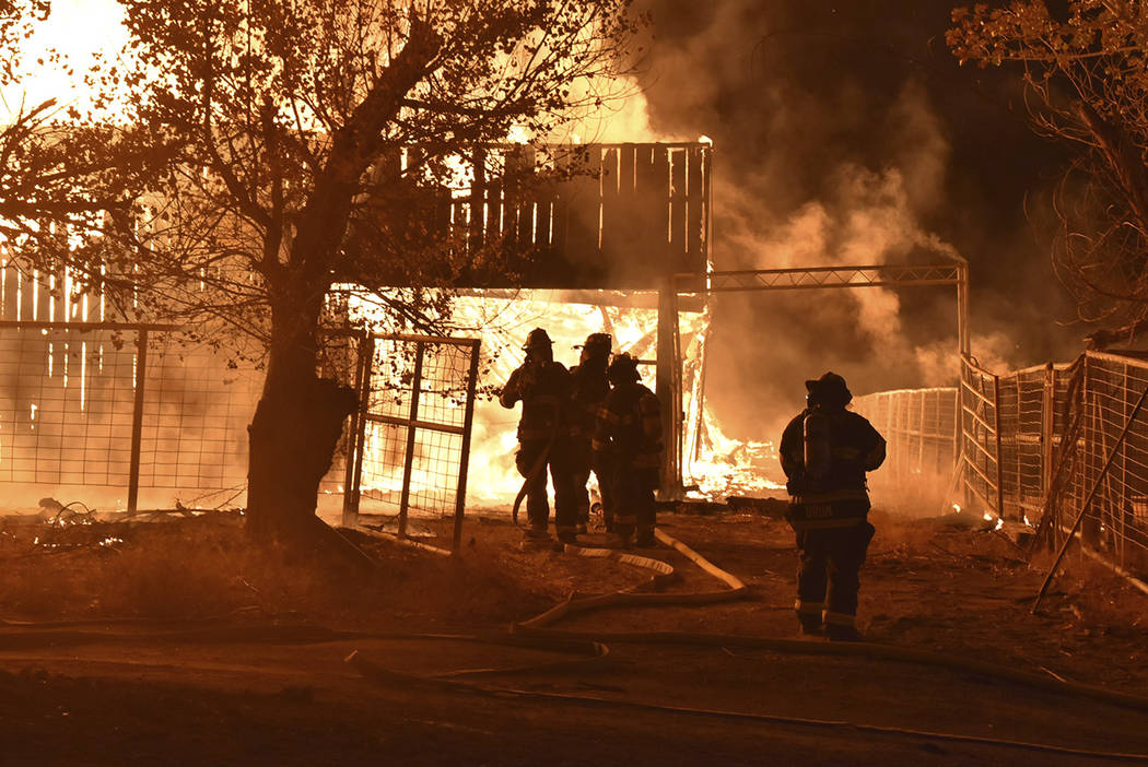 Crews at the scene of a fire that destroyed at least two structures on the historic Binion Ranc ...