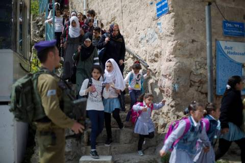 FILE - In this March 21, 2019 file photo, an Israeli solider stands guard as Palestinian school ...