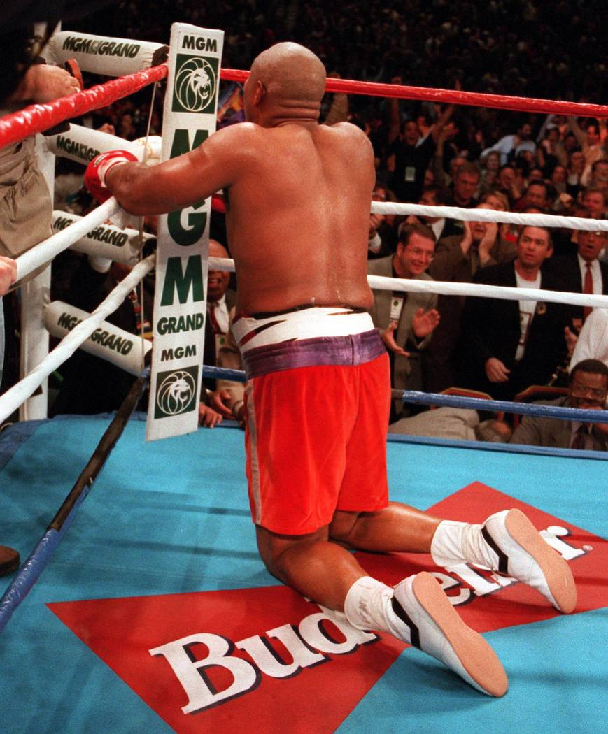 George Foreman kneels and prays after knocking out Michael Moorer in the 10th round for world h ...