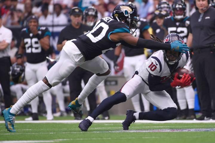 Houston Texans wide receiver DeAndre Hopkins (10) makes a catch in front of Jacksonville Jaguar ...