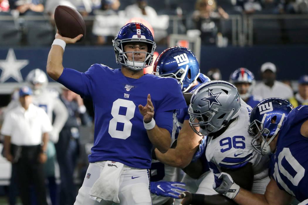 New York Giants quarterback Daniel Jones (8) throws a pass under pressure from Dallas Cowboys d ...