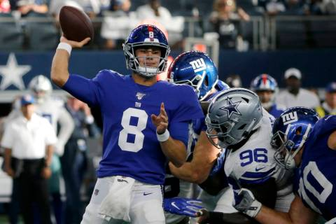 New York Giants quarterback Daniel Jones (8) throws a pass under pressure from Dallas Cowboys d ...
