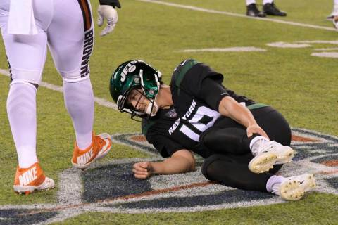 New York Jets quarterback Trevor Siemian (19) grabs his leg after being hurt during the first h ...