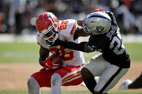 Kansas City Chiefs running back Damien Williams tries to break away from Oakland Raiders free s ...