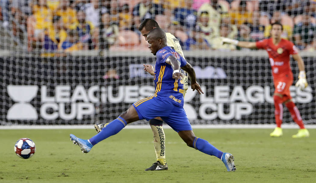 Tigres' Enner Valencia, front, moves the ball past Club America's Paul Aguilar, back, during th ...