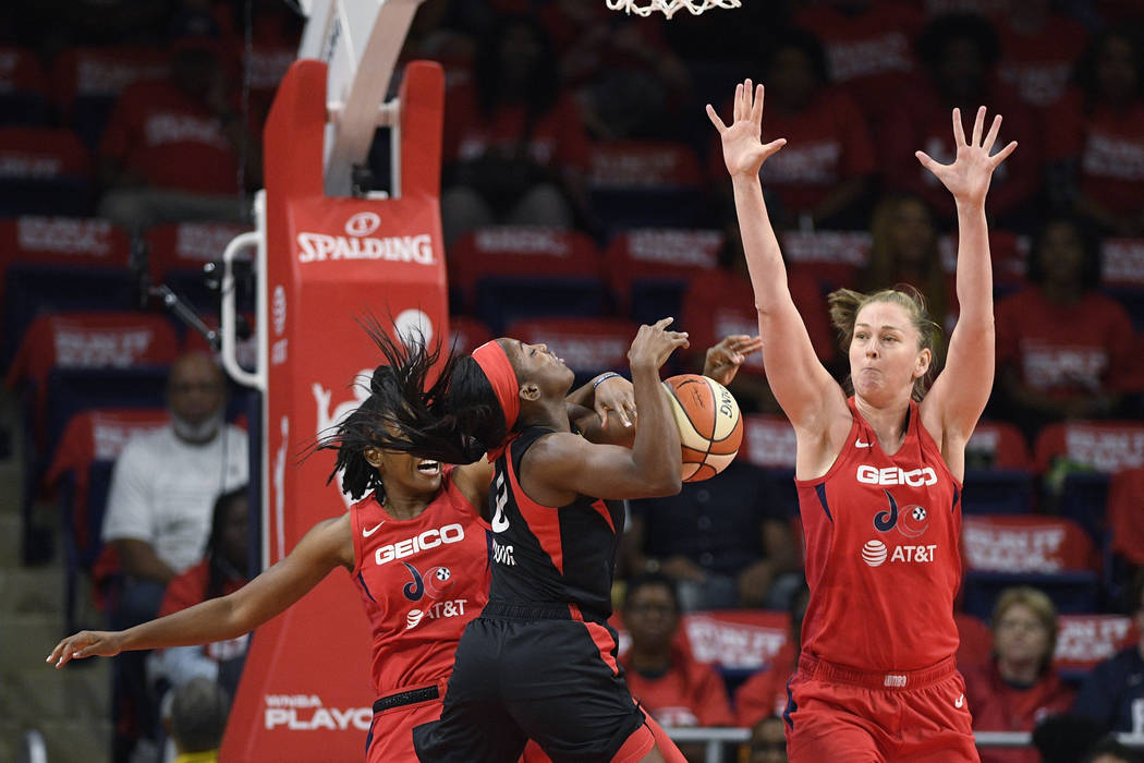 Washington Mystics guard Ariel Atkins, back left, fouls Las Vegas Aces guard Jackie Young (0) d ...