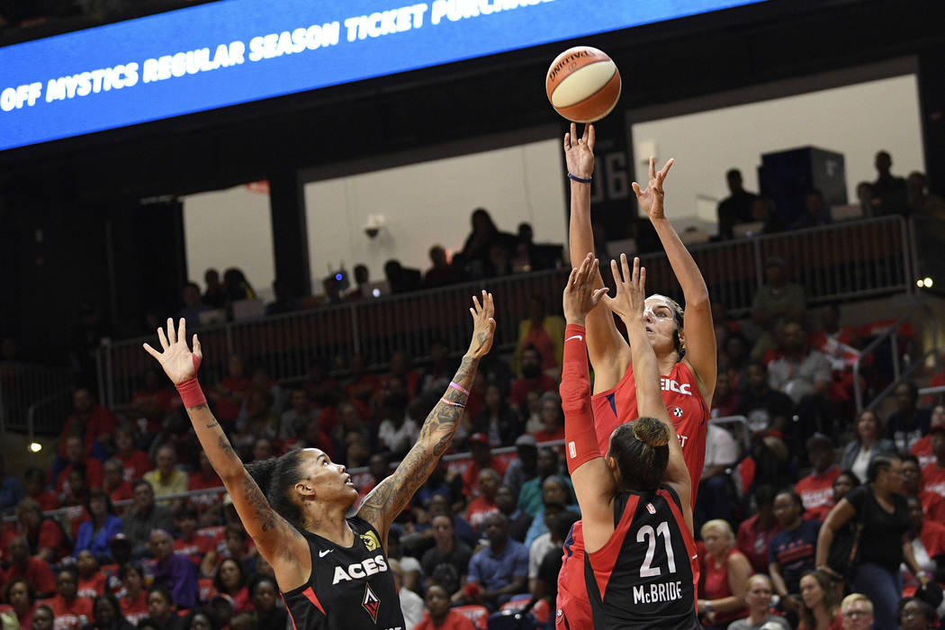 Washington Mystics forward Elena Delle Donne, back, shoots over Las Vegas Aces guard Kayla McBr ...