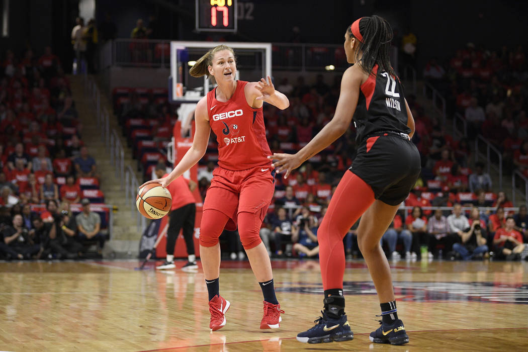 Washington Mystics center Emma Meesseman, left, dribbles the ball in front of Las Vegas Aces ce ...