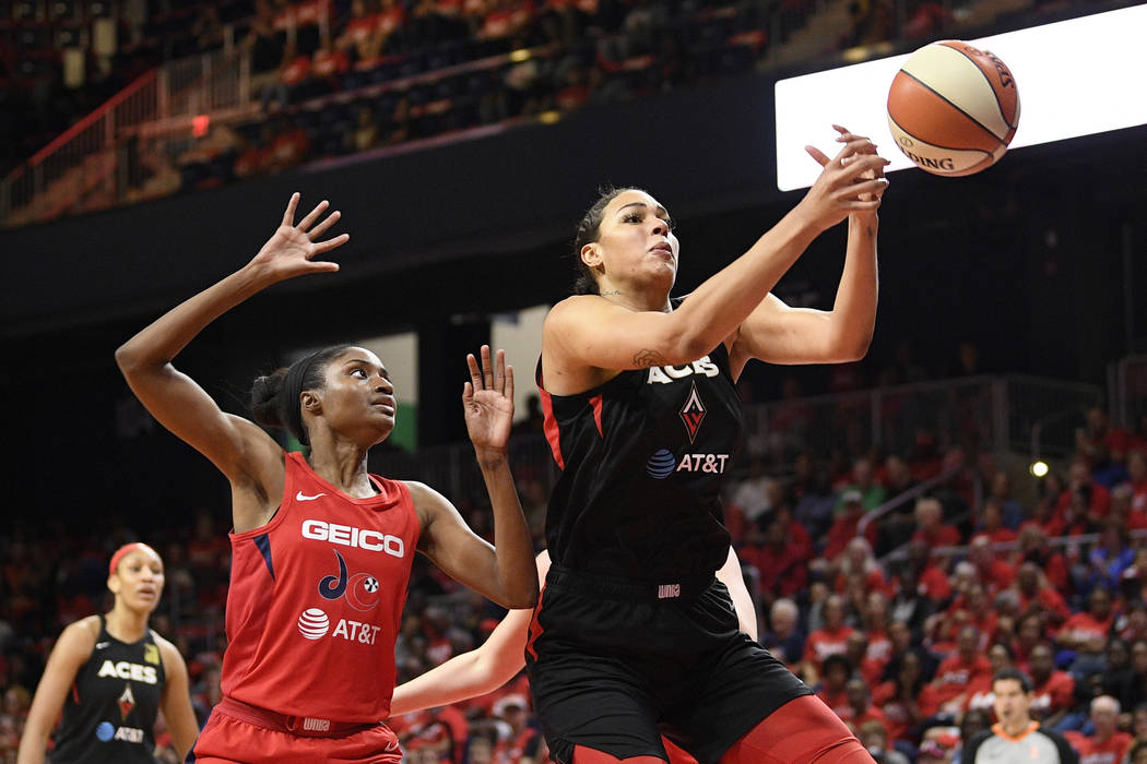 Las Vegas Aces center Liz Cambage, right, loses the ball as Washington Mystics forward LaToya S ...