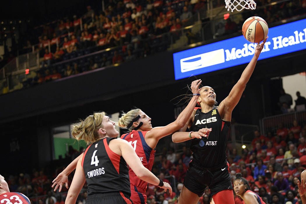 Las Vegas Aces center A'ja Wilson, right, goes to the basket against Washington Mystics forward ...