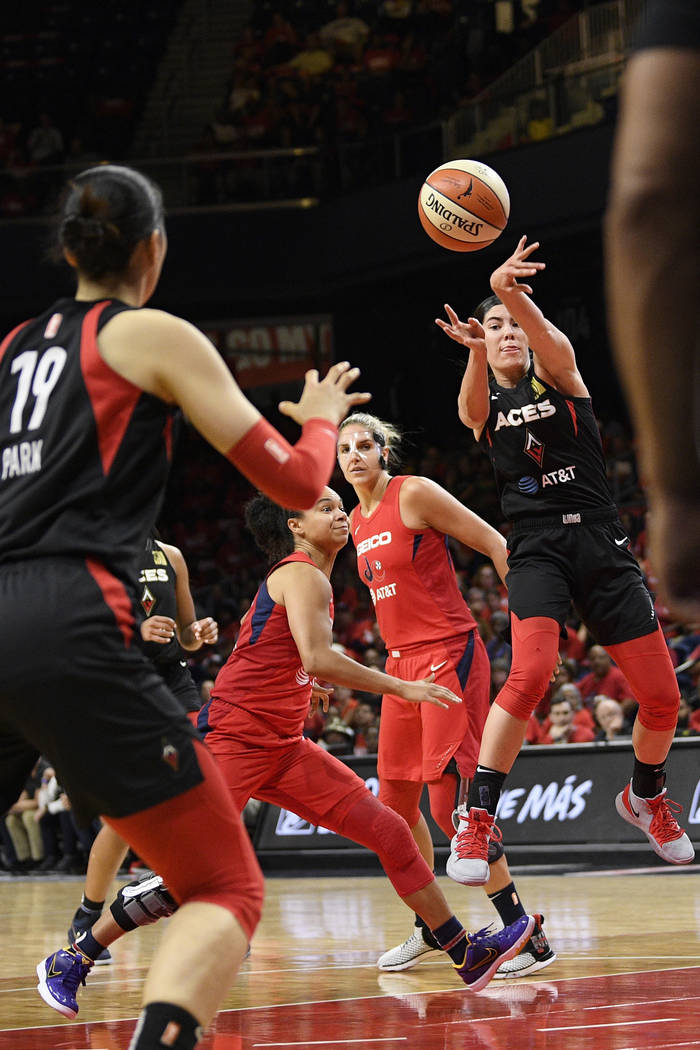 Las Vegas Aces guard Kelsey Plum, right, passes the ball toward center Ji-Su Park (19), past Wa ...