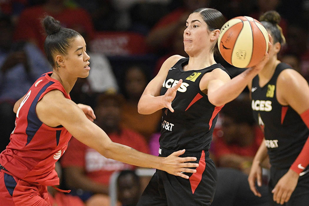 Las Vegas Aces guard Kelsey Plum, right, looks to pass the ball as Washington Mystics guard Nat ...