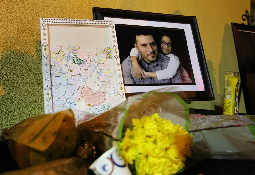 A bouquet of flowers lies next to a photograph of Mark Garcia and his daughter Monet during a c ...