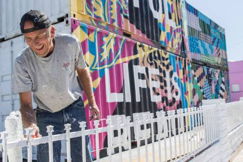 Jonathan Strublein paints a fence in preparation for Life is Beautiful music festival in downto ...