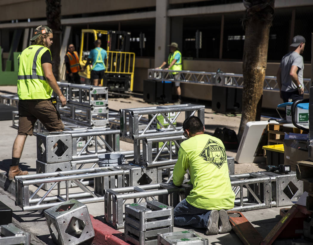 Workers build piping for stages at the intersection of North 7th Street and East Ogden Avenue i ...