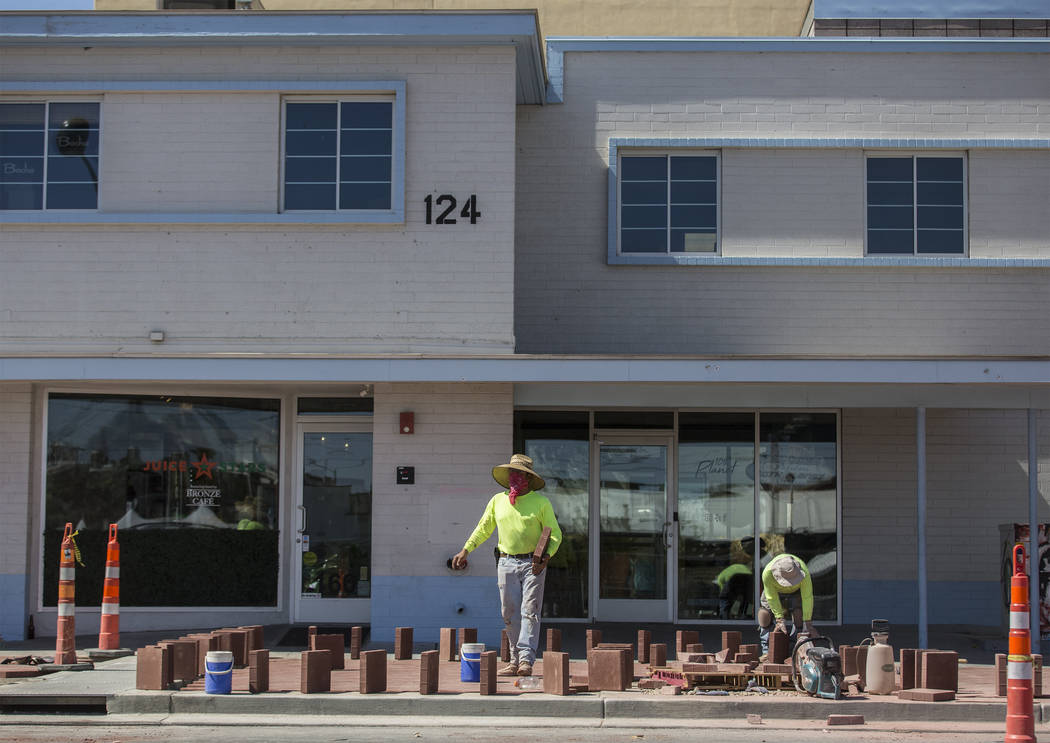 Construction workers lay brick at the intersection of South 6th Street and East Carson Avenue i ...