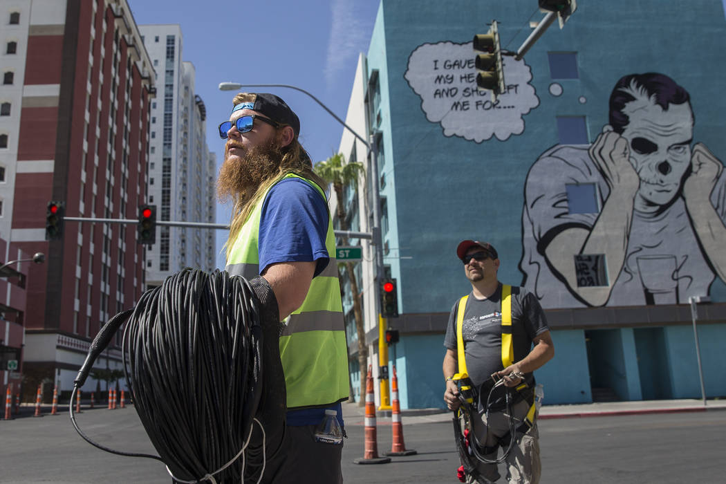 Big Vision entertainment workers Nick Werst, left, and Shane Smith run fiber for camera and vid ...