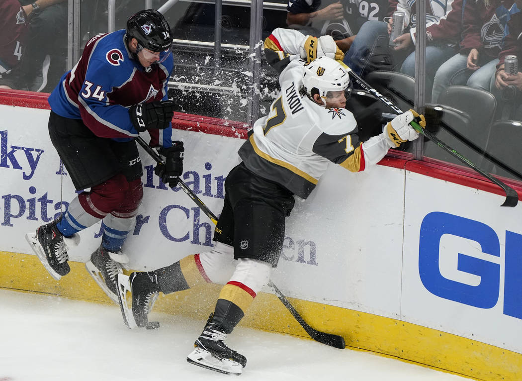Vegas Golden Knights left wing Valentin Zykov (7) crashes into the boards with Colorado Avalanc ...
