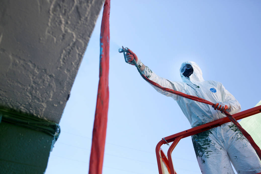 Producer Mike Bronke from Chicago paints a coat of vibrant paint for the Bacardi Art Motel in p ...